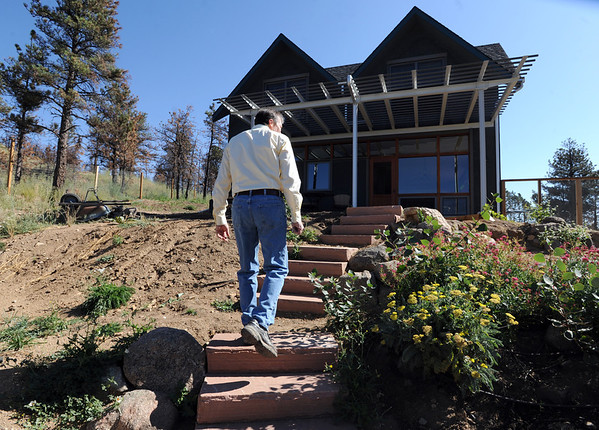 "Richard Nuzzi walks from the greenhouse to the new home in Sunshine Canyon.<br /> Richard Nuzzi and Stephanie O'Hearn are near completion of rebuilding their home after losing the previous one in the Four Mile Canyon Fire last year.<br /> For a video and more photos from the fire rebuilding, go to  <a href=""http://www.dailycamer.com"">http://www.dailycamer.com</a>.<br /> Cliff Grassmick / August 24, 2011"