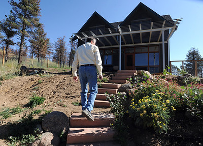 Richard Nuzzi walks from the greenhouse to the new home in Sunshine Canyon. Richard Nuzzi and Stephanie O'Hearn are near completion of rebuilding their home after losing the previous one in the Four Mile Canyon Fire last year. For a video and more photos from the fire rebuilding, go to www.dailycamer.com. Cliff Grassmick / August 24, 2011