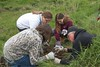 CSC grounds crew member Craig Price, right, shows Chadron Middle School students how to properly plant a golden currant near Eagle Ridge Monday, May 22, 2017. From left, Leah Weber, Angelina LaPorte and Hannah Wegesser. (Photo by Tena L. Cook/Chadron State College)