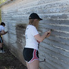 Chadron State College students Robert Cantril, left, and MacKenzie Bowker, right, scrape paint off a Chadron resident's garage during The Big Event Saturday, April 22, 2017. (Photo by Kelsey R. Brummels/Chadron State College)