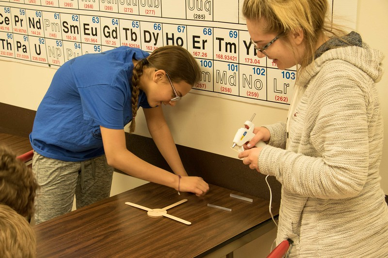 Chadron State College student Shannon Schneider, right, helps Blaine Tewahade, left,  glue together her anemometer during Science Saturday at Chadron State College Math and Science Building, Saturday, April 8, 2017.  (Photo by Alex Coon/Chadron State College)