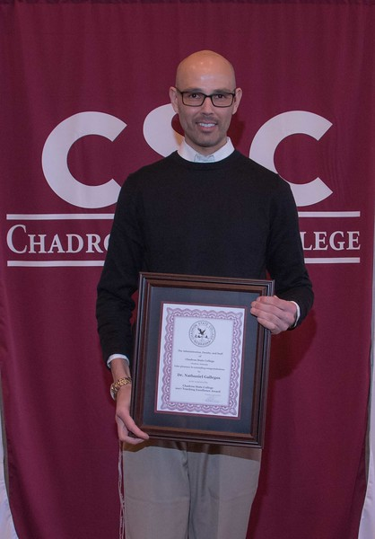 Dr. Nathaniel Gallegos poses with a plaque honoring him as the Chadron State College Teaching Excellence Award recipient at the annual Chadron State College Faculty and Staff Recognition Luncheon Thursday, April 13, 2017, in the Student Center Ballroom. (Photo by Tena L. Cook/Chadron State College)