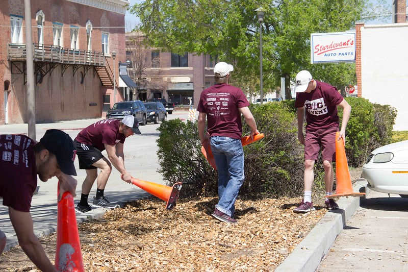 Members of the CSC wrestling team spread wood chips in planters on the city parking lot west of the 200 block of Main Street. (Photo by Tena L. Cook/Chadron State College)