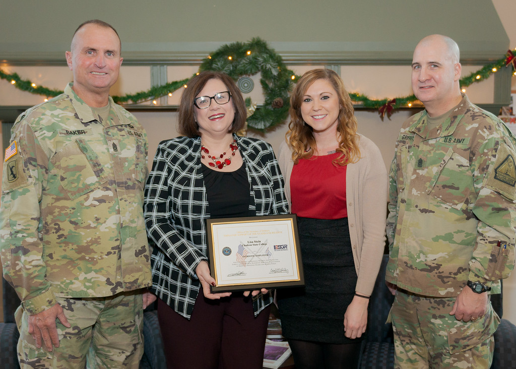 Chadron State College Director of Admissions Lisa Stein receives the Employer Support of the Guard and Reserve's Service Member Patriot Award Dec. 11, 2018, at Crites Hall. Stein was nominated for the award by service member and CSC Admissions Representative Heidi McClintock in recognition of Stein's support of McClintock. From left, Command Sgt. Maj. Marty Baker with the Nebraska Army National Guard, Stein, McClintock, and Command Sgt. Major of Recruiting and Retention Shawn Griffith with the Nebraska Army National Guard. (Photo by Daniel Binkard/Chadron State College)