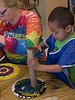 A student at Chadron State College's Child Development Center paints a colorful paper plate turtle shell during A Week of the Young Child activity, Thursday, April 18, 2018. (Photo by Tena L. Cook/Chadron State College)