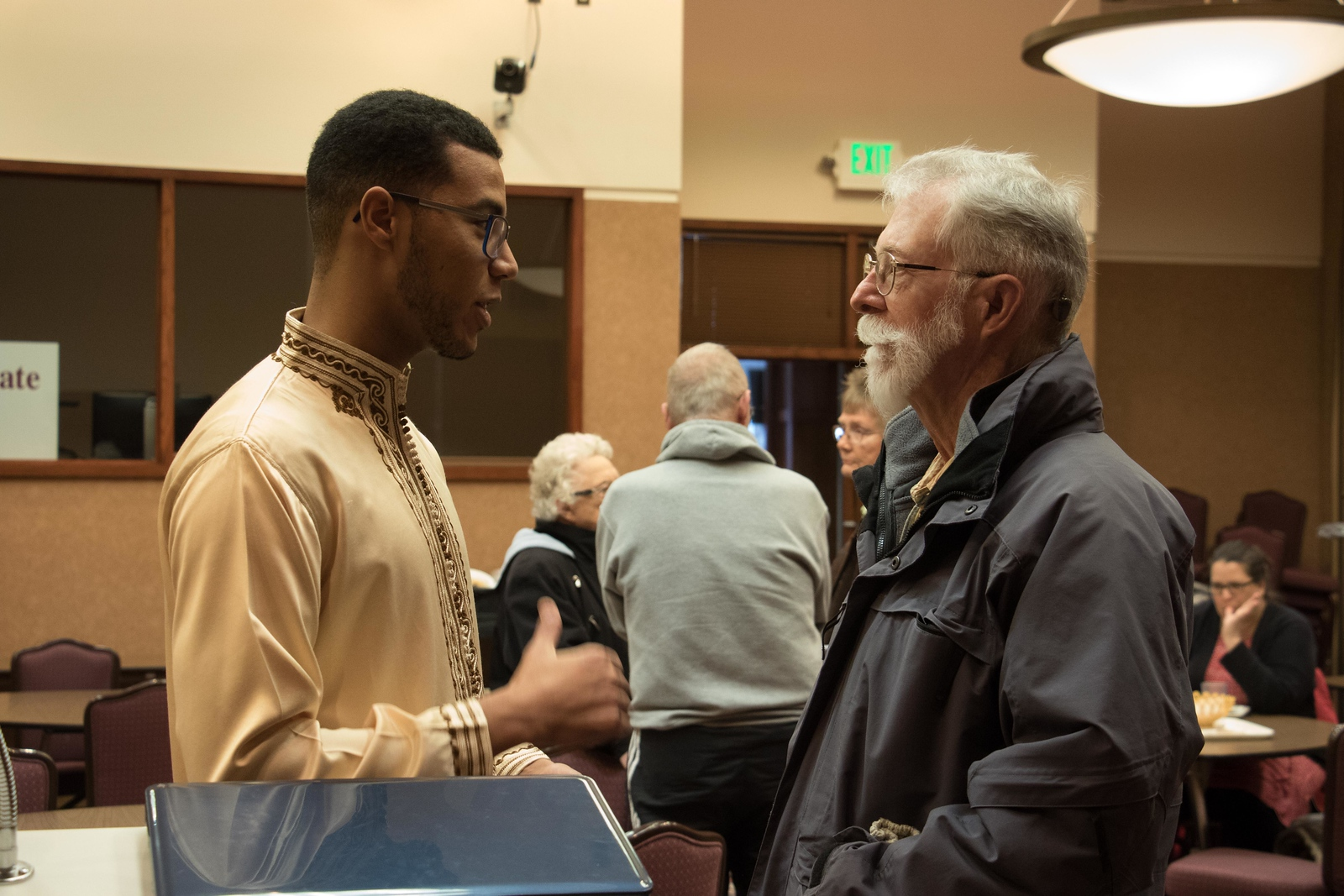 Chadron State College student Anas Haddadi, left, speaks with retired CSC professor Dr. Jim O'Rourke in the Student Center Thursday, Feb. 22, 2018, following Haddadi's presentation about his home country of Morocco during Dine With Us, a lunch series sponsored by the office of International Affairs. (Photo by Tena L. Cook/Chadron State College)