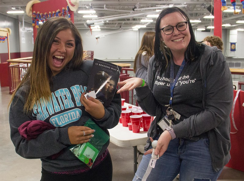 Aspen Eubanks of Broomfield, Colo., left, celebrates after winning a book at the Sigma Tau Delta booth during Spring Daze Friday 21, 2017. (Photo by Tena L. Cook/Chadron State College)