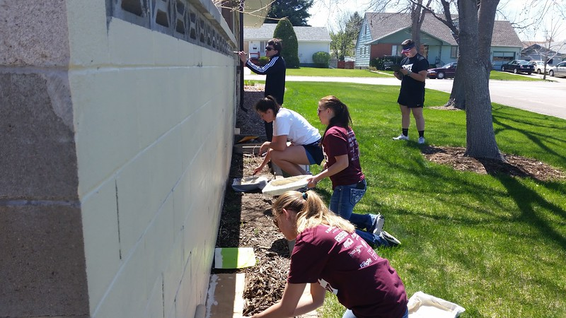 Chadron State College students paint a wall for a Chadron resident during The Big Event Saturday, April 22, 2017. (Photo by Alex Coon/Chadron State College)