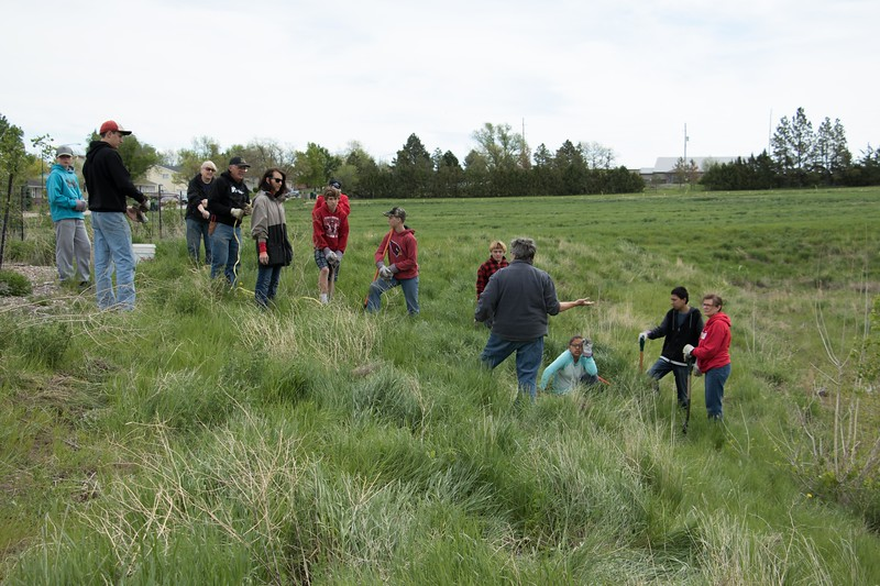 Chadron Middle School faculty and students listen to instruction by CSC horticulturist Lucinda Mays, center, during a project planting about 75 golden currants, chokecherries and wild American plums donated by the Upper Niobrara White Natural Resource District May 22, 2017 near Eagle Ridge. CMS and UNWNRD adults help supervise the project. (Photo by Tena L. Cook/Chadron State College)