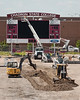 Workers finish attaching the Chadron State header to its position above the scoreboard while dirt work continues on Elliott Field at Beebe Stadium on June 29, 2018. Construction is expected to be largely complete for the first home football game of the 2018 season on September 1. (Photo by Daniel Binkard/Chadron State College)