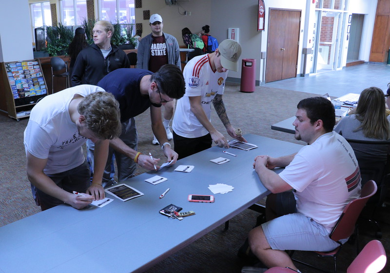 """Chadron State College students, from left, Johnny Dunn, Justin Brester  and  Isaiah Wilson, fill out a survey for Rulon Taylor in Weight of the Nation's """"Don't Drive In'Text'icated"""" program. (Photo by Alex Coon/Chadron State College)"""