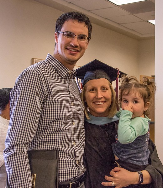 Chadron State College master's graduate Loni Watson, center, poses with her husband, Matt, and daughter, Reese, after commencement in Memorial Hall May 6, 2017. (Photo by Tena L. Cook/Chadron State College)