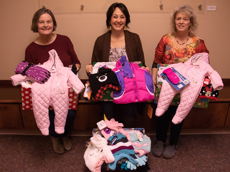 Chadron State College's Professional Staff Association collected 275 pairs of mittens, gloves and socks plus 104 hats and several other warm clothing items for children. From left, Tammy Zuver with Chadron Caring and Sharing , CSC employees Colette Fernandez and Sherrie Emerson pose Wednesday, Dec. 10, 2018, with the items that will be distributed to Chadron families in need. (Tena L. Cook/Chadron State College)