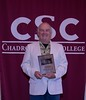 Dr. G. W. Sandy Schaefer poses with a plaque honoring him at the annual Chadron State College Faculty and Staff Recognition Luncheon Thursday, April 13, 2017, in the Student Center Ballroom. (Photo by Tena L. Cook/Chadron State College)