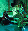 """Farrah the Fairy (Jacob Jensen) fights Agnes (Courtney Smith), front, and Tillius (Shanie Hollenbeck) during a """"Dungeons and Dragons"""" scene in """"She Kills Monsters"""" while dungeon master Biggs (Jarret Buchholz) runs the game. The play by Qui Nguyen was presented by the Chadron State College Theatre program. (Photo by Daniel Binkard/Chadron State College)"""