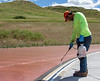 Michael Martinez with Beynon Sports Surfaces sprays primer on the Chadron State College track June 18, 2020, to prepare the surface for additional layers. (Photo by Tena L. Cook/Chadron State College)