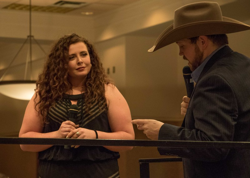 Chadron State College rodeo team member Elsie Fortune of Interior, S.D., left, is introduced by professional rodeo announcer and CSC alumnus Jared Slagle, right, during the Black Tie Calf Fry in the Student Center Friday, March 31, 2017. (Photo by Tena L. Cook/Chadron State College)