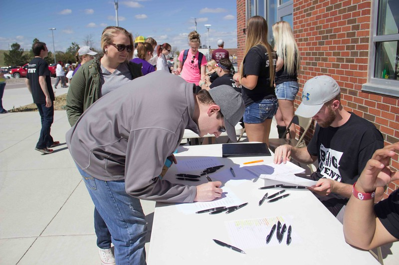 Jacob Rissler, left, signs in with Alex Coon, right, for The Big Event at the Chicoine Center Saturday, April 22, 2017. (Photo by Tena L. Cook/Chadron State College)