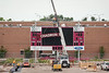 Workers lift the Chadron State header to its position above the scoreboard at Beebe Stadium on June 29, 2018. Construction is expected to be largely complete for the first home football game of the 2018 season on September 1. (Photo by Daniel Binkard/Chadron State College)