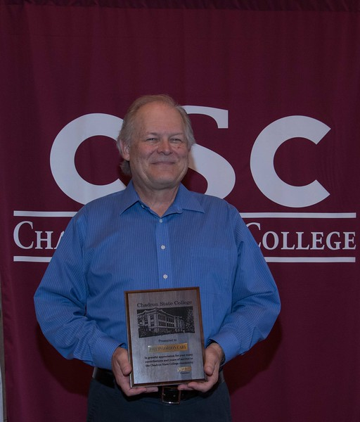 Phil Cary, retiring associate professor of mathematical sciences, poses with a plaque honoring him at the annual Chadron State College Faculty and Staff Recognition Luncheon Thursday, April 13, 2017, in the Student Center Ballroom. (Photo by Tena L. Cook/Chadron State College)