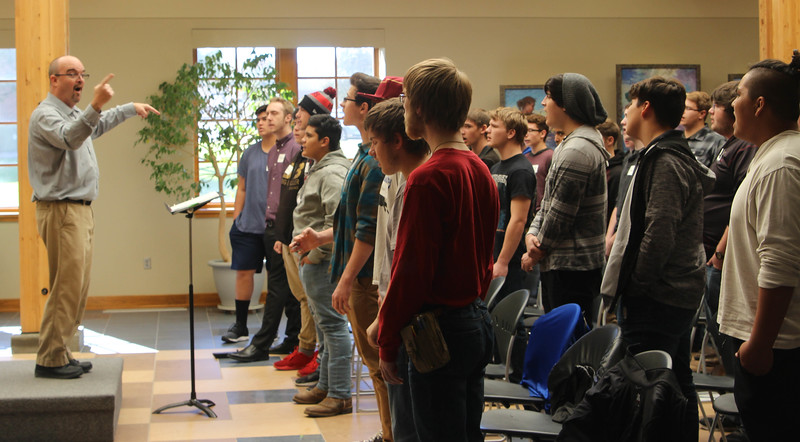 Dr. Joel Schreuder, Chadron State College professor of music, conducts Men's Choir Day attendees during a rehearsal session in the Sandoz Center's Chicoine Atrium, Wednesday, Oct. 17, 2018. (Photo by Kelsey R. Brummels/Chadron State College)