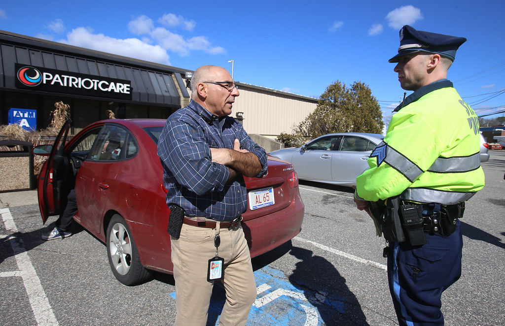 . First day of adult use recreational marijuana sales at Patriot Care in Lowell. George Agganis, VP of Security for Columbia Care, talks with State Police Sgt. Brad Sullivan. State Police were keeping an eye on the Lowell Connector in case traffic backed up at the Industrial Ave exit. (SUN Julia Malakie)