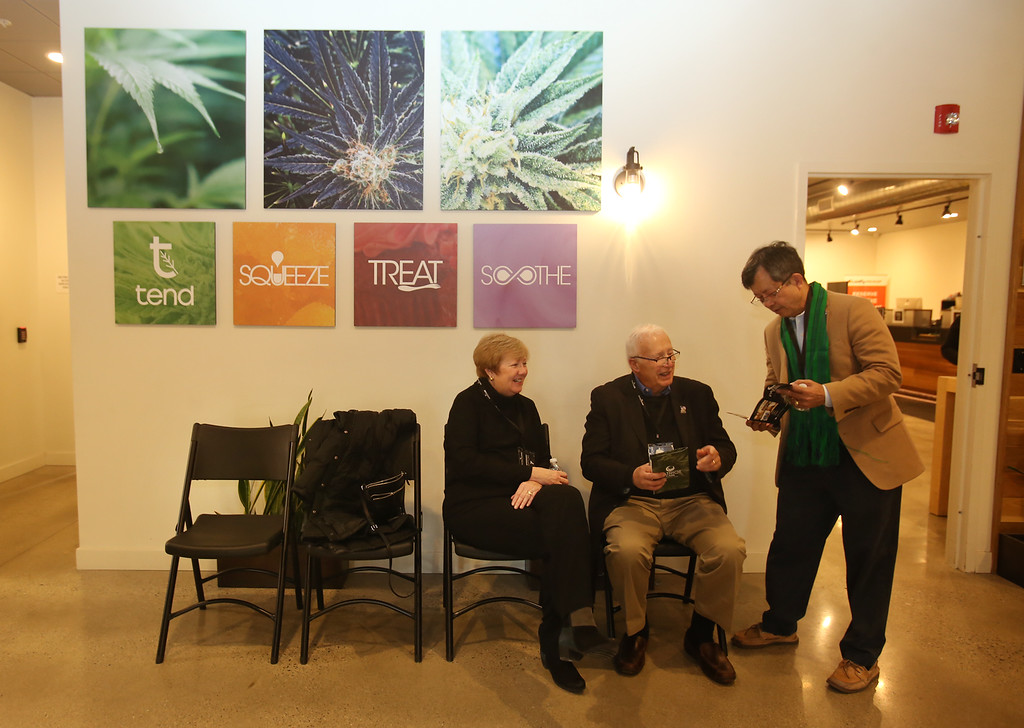 . First day of adult use recreational marijuana sales at Patriot Care in Lowell. City councilor Vesna Nuon shows Lowell city manager Eileen Donoghue and mayor Bill Samaras a brochure as they wait for the press event. (SUN Julia Malakie)