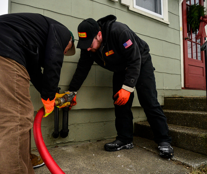 KRISTOPHER RADDER — BRATTLEBORO REFORMER<br /> U.S. Rep. Peter Welch, D-Vt., with help from Kevin Connors, a driver for Cota and Cota, delivers heating fuel to 121 Oak Grove Ave., in Brattleboro, as part of the Vermont Fuel Dealers Association's Split the Ticket Program on Friday, Dec. 13, 2019. The resident received 144 gallons of fuel through the program.