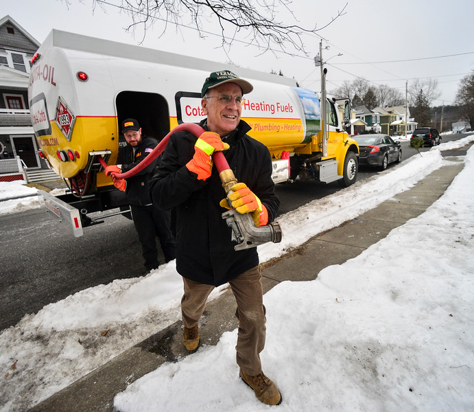 KRISTOPHER RADDER — BRATTLEBORO REFORMER<br /> U.S. Rep. Peter Welch, D-Vt., carries a fuel line from the Cota and Cota fuel truck to 121 Oak Grove Ave., in Brattleboro, as he helps deliver fuel to a Brattleboro resident as part of the Vermont Fuel Dealers Association's Split the Ticket Program on Friday, Dec. 13, 2019. The resident received 144 gallons of fuel through the program.