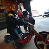 KRISTOPHER RADDER — BRATTLEBORO REFORMER<br /> Winchester Police Officer Bryan Jalava helps Jax Labby, 5, of Hinsdale, put a police sticker onto his new Big Wheel on Tuesday, Oct. 20, 2018.