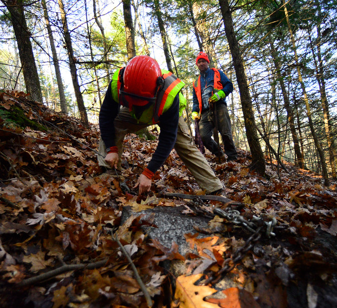 KRISTOPHER RADDER — BRATTLEBORO REFORMER<br /> Brian Post works on putting a chain around one of the caps before dragging it back up to the base of the Retreat Tower on Thursday, Nov. 21, 2019.