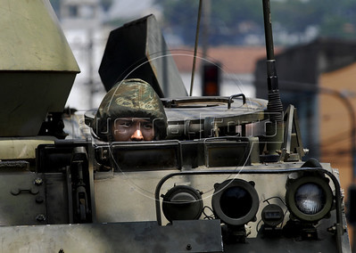 A marine looks out over an armoured vehicle during an operation at Complexo da Penha, Rio de Janeiro, Brazil, November 25, 2010. Authorities in Rio de Janeiro try to control a fourth day of violence apparently orchestrated by drug gang members who have attacked police stations and burned cars in Rio de Janeiro city as protest by traffickers after being forced from their turf by police occupations of more than a dozen slums in the past two years. (Austral Foto/Renzo Gostoli)