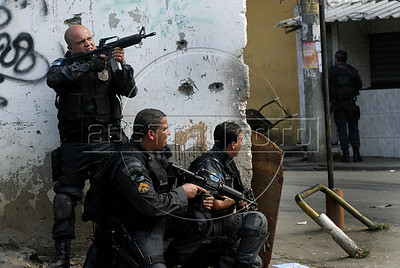 Policemen take position during operation at Vila Cruzeiro slum, Rio de Janeiro, Brazil, November 25, 2010. Authorities in Rio de Janeiro try to control a fourth day of violence apparently orchestrated by drug gang members who have attacked police stations and burned cars in Rio de Janeiro city as protest by traffickers after being forced from their turf by police occupations of more than a dozen slums in the past two years. (Austral Foto/Renzo Gostoli)