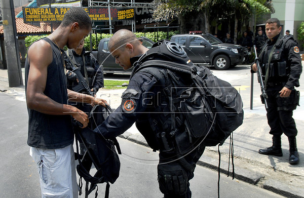 A policeman checks a suspect at Complexo da Penha, Rio de Janeiro, Brazil, November 25, 2010. Authorities in Rio de Janeiro try to control a fourth day of violence apparently orchestrated by drug gang members who have attacked police stations and burned cars in Rio de Janeiro city as protest by traffickers after being forced from their turf by police occupations of more than a dozen slums in the past two years.<br /> (Austral Foto/Renzo Gostoli)