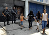 A family runs past policemen taking positions during an operation against drug traffickers in the Complexo da Penha, Rio de Janeiro, Brazil, November 25, 2010. Authorities in Rio de Janeiro try to control a fourth day of violence apparently orchestrated by drug gang members who have attacked police stations and burned cars in Rio de Janeiro city as protest by traffickers after being forced from their turf by police occupations of more than a dozen slums in the past two years.<br /> (Austral Foto/Renzo Gostoli)