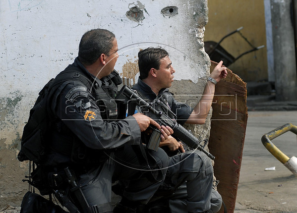 Policemen take position during operation at Vila Cruzeiro slum, Rio de Janeiro, Brazil, November 25, 2010. Authorities in Rio de Janeiro try to control a fourth day of violence apparently orchestrated by drug gang members who have attacked police stations and burned cars in Rio de Janeiro city as protest by traffickers after being forced from their turf by police occupations of more than a dozen slums in the past two years.<br /> (Austral Foto/Renzo Gostoli)