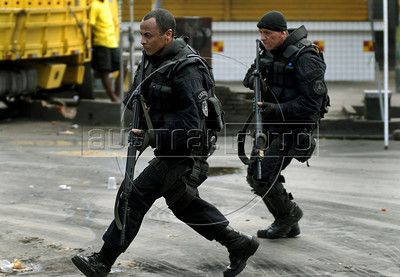 Policemen run during a attack to trafficker at Vila Cruzeiro slum, Rio de Janeiro, Brazil, November 25, 2010. Authorities in Rio de Janeiro try to control a fourth day of violence apparently orchestrated by drug gang members who have attacked police stations and burned cars in Rio de Janeiro city as protest by traffickers after being forced from their turf by police occupations of more than a dozen slums in the past two years. (Austral Foto/Renzo Gostoli)