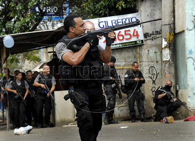 A policeman shoots his gun during a operation at Vila Cruzeiro slum, Rio de Janeiro, Brazil, November 25, 2010. Authorities in Rio de Janeiro try to control a fourth day of violence apparently orchestrated by drug gang members who have attacked police stations and burned cars in Rio de Janeiro city as protest by traffickers after being forced from their turf by police occupations of more than a dozen slums in the past two years. (Austral Foto/Renzo Gostoli)