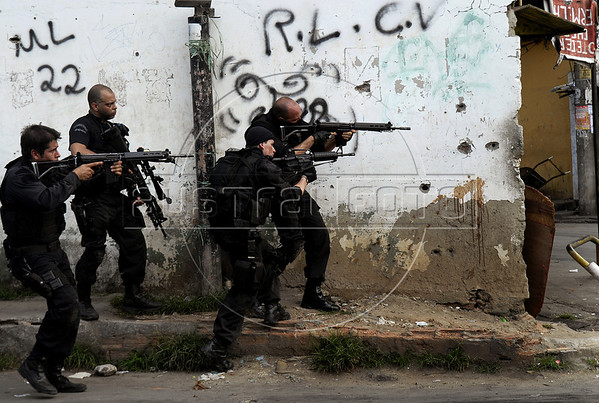 Policemen take position during a operation at Vila Cruzeiro slum, Rio de Janeiro, Brazil, November 25, 2010. Authorities in Rio de Janeiro try to control a fourth day of violence apparently orchestrated by drug gang members who have attacked police stations and burned cars in Rio de Janeiro city as protest by traffickers after being forced from their turf by police occupations of more than a dozen slums in the past two years.<br /> (Austral Foto/Renzo Gostoli)
