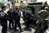 Policemen enter an armored Navy vehicle during an operation at Vila Cruzeiro slum, Rio de Janeiro, Brazil, November 25, 2010. Authorities in Rio de Janeiro try to control a fourth day of violence apparently orchestrated by drug gang members who have attacked police stations and burned cars in Rio de Janeiro city as protest by traffickers after being forced from their turf by police occupations of more than a dozen slums in the past two years. (Austral Foto/Renzo Gostoli)