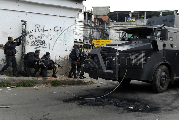 Policemen and an armored police vehicle participate at a operation at Vila Cruzeiro slum, Rio de Janeiro, Brazil, November 25, 2010. Authorities in Rio de Janeiro try to control a fourth day of violence apparently orchestrated by drug gang members who have attacked police stations and burned cars in Rio de Janeiro city as protest by traffickers after being forced from their turf by police occupations of more than a dozen slums in the past two years.<br /> (Austral Foto/Renzo Gostoli)