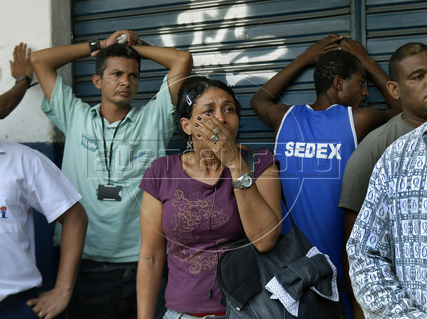 People detained by police waits to be checked at Vila Cruzeiro slum, Rio de Janeiro, Brazil, November 25, 2010. Authorities in Rio de Janeiro try to control a fourth day of violence apparently orchestrated by drug gang members who have attacked police stations and burned cars in Rio de Janeiro city as protest by traffickers after being forced from their turf by police occupations of more than a dozen slums in the past two years. (Austral Foto/Renzo Gostoli)