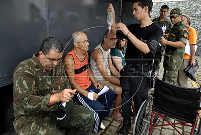 Volunteers and soldiers assist victims of landslides at a Brazilian Navy hospital in Nova Friburgo, Rio de Janeiro state, Brazil, January 15, 2011. After six days of torrential rains, mudslides have killed more than 640 people in the Rio de Janeiro area. (Austral Foto/Renzo Gostoli)