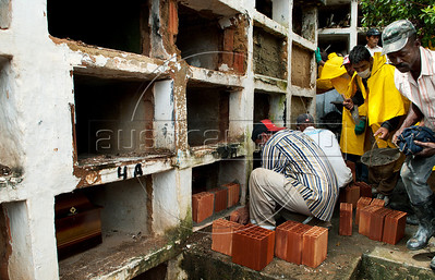 Workers bury coffins containing remains not identified of people killed by landslides at Sao Joao Baptista cemetery in Nova Friburgo, Rio de Janeiro state, Brazil, January 15, 2011. After six days of torrential rains, mudslides have killed more than 640 people in the Rio de Janeiro area. (Austral Foto/Renzo Gostoli)