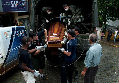 Army soldiers and volunteers unload coffins containing remains of people killed by landslides at the morgue in Nova Friburgo, Rio de Janeiro state, Brazil, January 15, 2011. After six days of torrential rains, mudslides have killed more than 640 people in the Rio de Janeiro area. (Austral Foto/Renzo Gostoli)