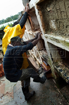 A worker buries coffins containing remains of people killed by landslides at the morgue in Nova Friburgo, Rio de Janeiro state, Brazil, January 15, 2011. After six days of torrential rains, mudslides have killed more than 640 people in the Rio de Janeiro area. (Austral Foto/Renzo Gostoli)
