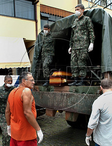 Army soldiers and volunteers wait to carry coffins containing remains of people killed by landslides at the morgue in Nova Friburgo, Rio de Janeiro state, Brazil, January 15, 2011. After six days of torrential rains, mudslides have killed more than 640 people in the Rio de Janeiro area. (Austral Foto/Renzo Gostoli)