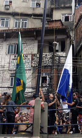 Military police raise the  Rio de Janeiro's, right, and Brazilian, left, flags at the Rocinha shantytown, Rio de Janeiro, Brazil, November 13, 2011. (Austral Foto/Renzo Gostoli)