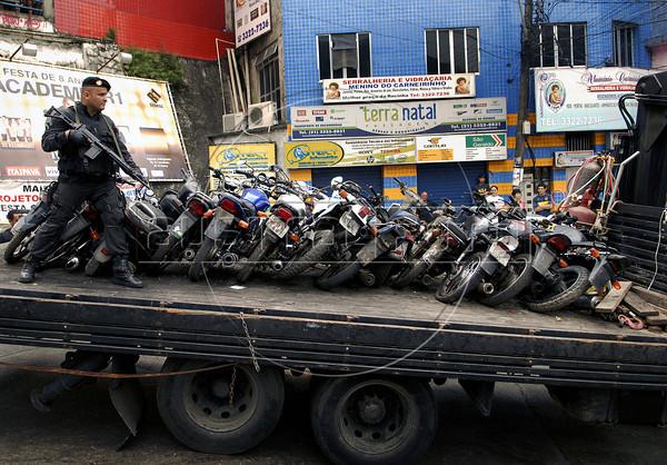 A military police guards stolen motorcycles carried in a truck at the Rocinha shantytown, Rio de Janeiro, Brazil, November 13, 2011. (Austral Foto/Renzo Gostoli)