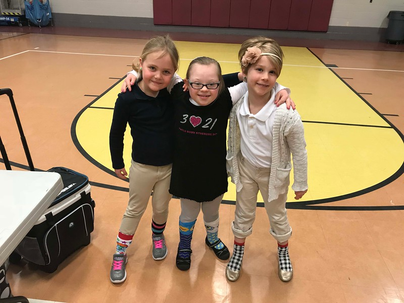 NATHAN HAVENNER / GAZETTE  Grace Paul, 7, center, poses with friends Bella Good, left, and Olivia Stahnke, from Mona Smith's first-grade class at Medina Christian Academy during lunch Thursday. Students wore crazy socks to celebrate Grace and World Down Syndrome Day.